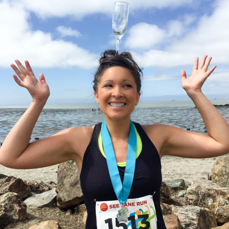 Balancing my finisher's champagne glass on my head after running the See Jane Run Half Marathon San Francisco race in Alameda